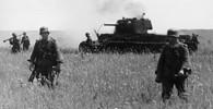 Postupující německá pěchota, v pozadí zničený sovětský tank KV-1