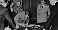 Adolf Hitler při podepisování Mnichovské dohody dne 29. září 1938. Vzadu v pozadí stojí říšský maršál Hermann Göring, který diskutuje s italským vůdcem Benitem Mussolinim. Vedle Hitlera stojí v uniformě SS jeho pobočník Julius Schaub a muž vpravo v obleku opřený o stůl je říšský ministr zahraničí Joachim von Ribbentrop.
